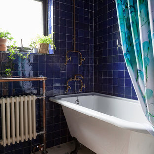 Bohemian ensuite bathroom in London with a claw-foot bath, a shower/bath combination, blue tiles, blue walls, multi-coloured floors and a shower curtain.
