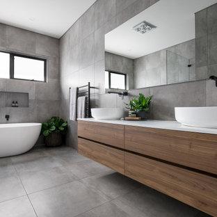 Diseño de cuarto de baño contemporáneo con armarios con paneles lisos, puertas de armario de madera oscura, bañera exenta, baldosas y/o azulejos grises, lavabo sobreencimera, suelo gris y encimeras blancas