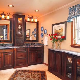 Inspiration for a large mediterranean ensuite bathroom in Cincinnati with beaded cabinets, dark wood cabinets, beige tiles, beige walls, travertine flooring, a submerged sink, granite worktops and beige floors.