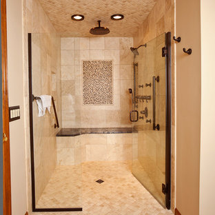 Example of a large tuscan master beige tile and stone tile travertine floor and beige floor walk-in shower design in Cincinnati with beige walls and a hinged shower door
