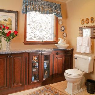 Photo of a large mediterranean ensuite bathroom in Cincinnati with beaded cabinets, dark wood cabinets, a two-piece toilet, beige tiles, beige walls, travertine flooring, a submerged sink, granite worktops and beige floors.