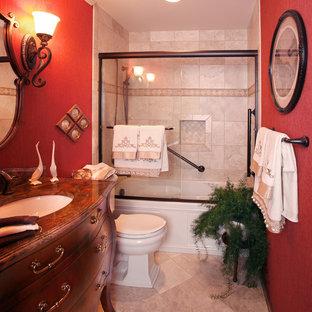 Inspiration for a small traditional master bathroom in Cincinnati with furniture-like cabinets, dark wood cabinets, an alcove tub, a shower/bathtub combo, a two-piece toilet, beige tile, ceramic tile, red walls, travertine floors, an undermount sink, solid surface benchtops, beige floor and a sliding shower screen.