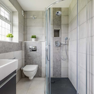 Photo of a medium sized contemporary shower room in London with flat-panel cabinets, a wall mounted toilet, grey tiles, stone tiles, grey walls, porcelain flooring, beige floors, black cabinets, a corner shower, a console sink and a sliding door.