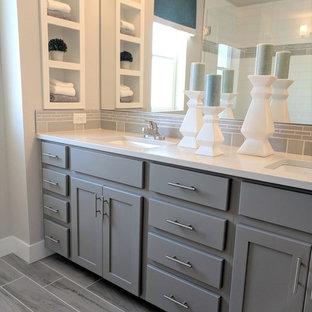 Mittelgroßes Modernes Badezimmer En Suite mit Schrankfronten im Shaker-Stil, grauen Schränken, Toilette mit Aufsatzspülkasten, weißen Fliesen, Keramikfliesen, grauer Wandfarbe, Porzellan-Bodenfliesen, Unterbauwaschbecken, Quarzwerkstein-Waschtisch, grauem Boden, weißer Waschtischplatte, Duschnische und Falttür-Duschabtrennung in Denver