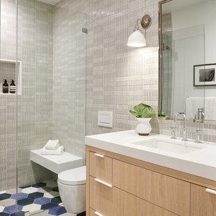 サンフランシスコの大きいトランジショナルスタイルのおしゃれな子供用バスルーム (フラットパネル扉のキャビネット、淡色木目調キャビネット、段差なし、壁掛け式トイレ、セラミックタイル、セメントタイルの床、アンダーカウンター洗面器、珪岩の洗面台、青い床、開き戸のシャワー、白い洗面カウンター、グレーのタイル) の写真