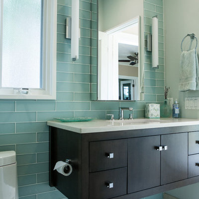 Corner shower - small eclectic green tile and glass tile porcelain tile corner shower idea in New York with an undermount sink, flat-panel cabinets, dark wood cabinets, quartz countertops, a two-piece toilet and blue walls