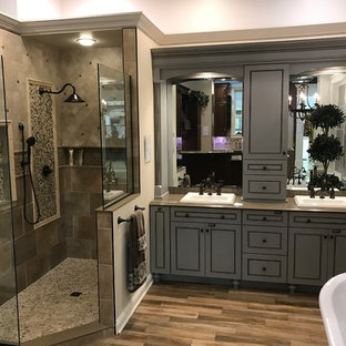 Medium sized mediterranean ensuite bathroom in Cleveland with beaded cabinets, grey cabinets, a freestanding bath, a corner shower, beige tiles, ceramic tiles, a built-in sink, solid surface worktops, a hinged door, a two-piece toilet, beige walls, medium hardwood flooring and brown floors.