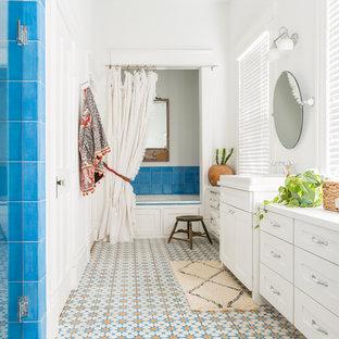 Ispirazione per una stanza da bagno padronale stile americano di medie dimensioni con ante in stile shaker, ante bianche, piastrelle blu, pareti bianche, porta doccia a battente, vasca ad alcova, doccia alcova, piastrelle in ceramica, pavimento con piastrelle in ceramica, lavabo da incasso e pavimento multicolore