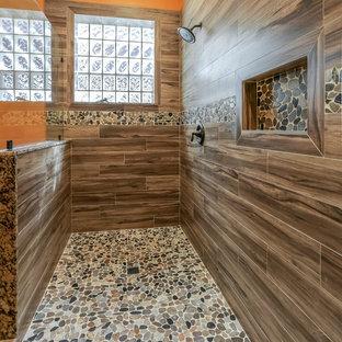 ヒューストンの広いサンタフェスタイルのおしゃれなマスターバスルーム (インセット扉のキャビネット、緑のキャビネット、ダブルシャワー、分離型トイレ、茶色いタイル、磁器タイル、オレンジの壁、磁器タイルの床、アンダーカウンター洗面器、御影石の洗面台) の写真
