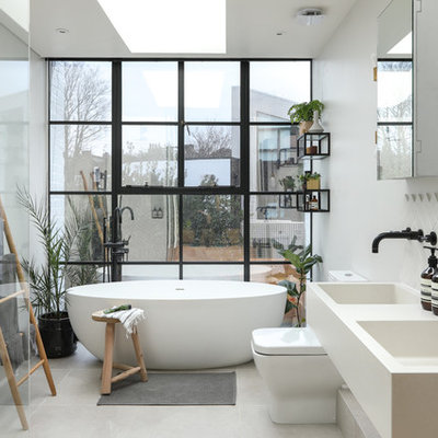 Example of a large danish 3/4 gray tile and ceramic tile ceramic tile and white floor bathroom design in London with white cabinets, a one-piece toilet, white walls, a wall-mount sink, marble countertops and white countertops
