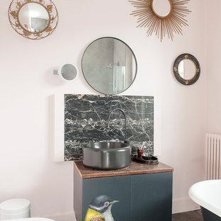 Großes Stilmix Kinderbad mit flächenbündigen Schrankfronten, schwarzen Schränken, Löwenfuß-Badewanne, Steinplatten, beiger Wandfarbe, dunklem Holzboden, Aufsatzwaschbecken, Waschtisch aus Holz und Toilette mit Aufsatzspülkasten in Sussex