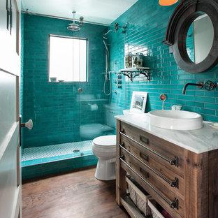 Modelo de cuarto de baño con ducha, bohemio, pequeño, con armarios tipo mueble, ducha empotrada, sanitario de una pieza, baldosas y/o azulejos azules, baldosas y/o azulejos de cerámica, paredes grises, suelo de madera en tonos medios, lavabo sobreencimera, encimera de mármol y puertas de armario de madera en tonos medios