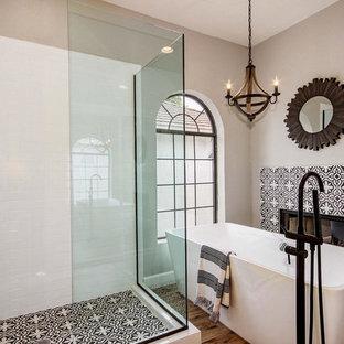 Large mediterranean ensuite bathroom in Phoenix with a freestanding bath, a corner shower, a hinged door, black and white tiles, multi-coloured tiles, cement tiles, brown walls, medium hardwood flooring and multi-coloured floors.