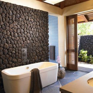 Idéer för tropiska badrum, med ett fristående badkar och skiffergolv