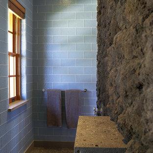 Esempio di una stanza da bagno tropicale con piastrelle di vetro, piastrelle blu, pavimento con piastrelle di ciottoli e pavimento beige
