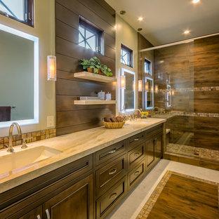 Foto di una grande stanza da bagno padronale tropicale con ante con riquadro incassato, ante in legno bruno, doccia aperta, piastrelle beige, piastrelle di vetro, pareti beige, pavimento in travertino, lavabo a bacinella e top in granito