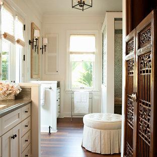 Foto de cuarto de baño principal, tropical, de tamaño medio, con suelo marrón, armarios estilo shaker, puertas de armario blancas, ducha esquinera, paredes blancas, suelo de madera oscura, lavabo bajoencimera y encimera de granito