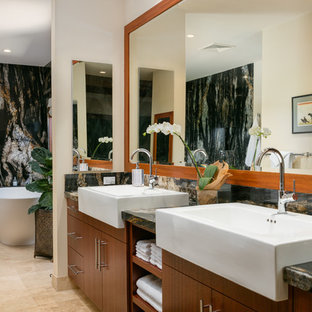 Example of an island style master multicolored tile beige floor and ceramic floor freestanding bathtub design in Hawaii with flat-panel cabinets, dark wood cabinets, beige walls, limestone countertops and a trough sink