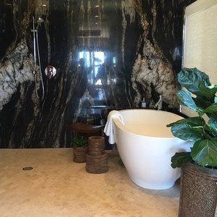 Foto de cuarto de baño principal, exótico, con armarios con paneles lisos, puertas de armario de madera en tonos medios, bañera exenta, baldosas y/o azulejos multicolor, paredes beige, suelo de baldosas de cerámica y encimera de piedra caliza