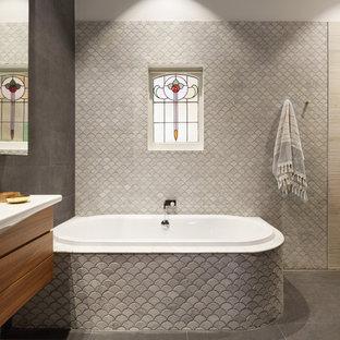 Diseño de cuarto de baño principal, actual, de tamaño medio, con ducha abierta, baldosas y/o azulejos grises, ducha abierta, armarios tipo vitrina, puertas de armario de madera oscura, bañera esquinera, suelo de baldosas tipo guijarro, lavabo sobreencimera y encimera de laminado