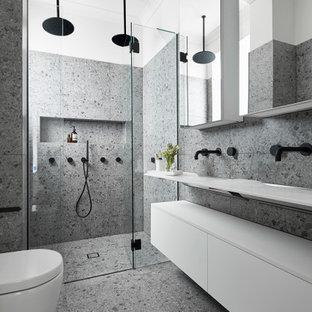 Пример оригинального дизайна: главная ванная комната среднего размера в современном стиле с белыми фасадами, двойным душем, инсталляцией, серой плиткой, плиткой из листового камня, серыми стенами, полом из терраццо, подвесной раковиной, столешницей из ламината, серым полом, душем с распашными дверями, белой столешницей и фасадами островного типа