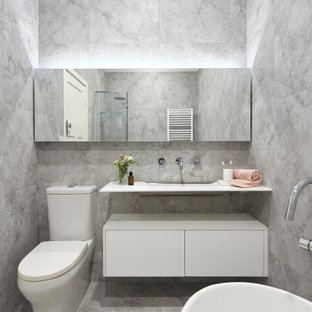 Photo of a small contemporary 3/4 bathroom in Melbourne with white cabinets, a freestanding tub, a corner shower, a wall-mount toilet, gray tile, stone tile, grey walls, marble floors, a console sink, laminate benchtops, grey floor, a hinged shower door, white benchtops and furniture-like cabinets.