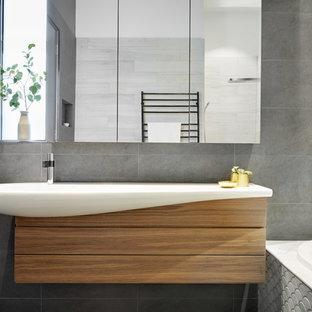 Diseño de cuarto de baño principal, actual, de tamaño medio, con armarios tipo vitrina, puertas de armario de madera oscura, bañera esquinera, ducha abierta, suelo de baldosas tipo guijarro, lavabo sobreencimera y encimera de laminado
