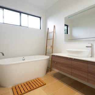 Photo of a contemporary 3/4 bathroom in Brisbane with medium wood cabinets, a freestanding tub, a vessel sink, beige floor and white benchtops.