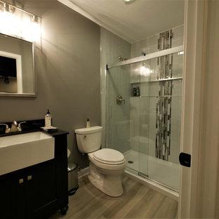 Esempio di una stanza da bagno con doccia tradizionale di medie dimensioni con ante nere, doccia alcova, WC a due pezzi, piastrelle grigie, piastrelle a listelli, pareti grigie, pavimento in laminato, top piastrellato, pavimento grigio, porta doccia scorrevole e top nero