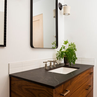Inspiration for a 1960s 3/4 white tile and ceramic tile mosaic tile floor and gray floor bathroom remodel in Seattle with medium tone wood cabinets, a one-piece toilet, white walls, an undermount sink, quartz countertops and black countertops