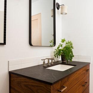 60 tals inredning av ett svart svart badrum med dusch, med skåp i mellenmörkt trä, en kantlös dusch, en toalettstol med hel cisternkåpa, vit kakel, keramikplattor, vita väggar, mosaikgolv, ett undermonterad handfat, bänkskiva i kvarts, grått golv och med dusch som är öppen