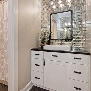 На фото: маленькая детская ванная комната в стиле неоклассика (современная классика) с фасадами в стиле шейкер, белыми фасадами, ванной в нише, душем в нише, разноцветной плиткой, зеркальной плиткой, бежевыми стенами, полом из керамогранита, накладной раковиной, столешницей из гранита, серым полом и шторкой для ванной с