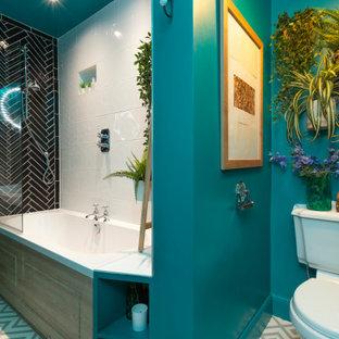 エディンバラの中くらいのエクレクティックスタイルのおしゃれな子供用バスルーム (ドロップイン型浴槽、シャワー付き浴槽、一体型トイレ、モノトーンのタイル、セラミックタイル、緑の壁、リノリウムの床、壁付け型シンク、タイルの洗面台、グレーの床、開き戸のシャワー、白い洗面カウンター) の写真
