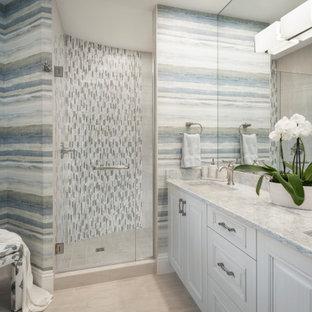 マイアミのビーチスタイルのおしゃれなバスルーム (浴槽なし) (レイズドパネル扉のキャビネット、白いキャビネット、コーナー設置型シャワー、マルチカラーのタイル、ボーダータイル、マルチカラーの壁、アンダーカウンター洗面器、ベージュの床、開き戸のシャワー、マルチカラーの洗面カウンター、洗面台2つ、フローティング洗面台、壁紙) の写真
