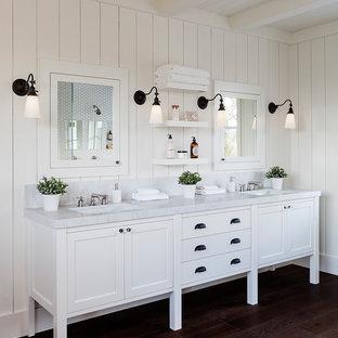 Imagen de cuarto de baño principal, campestre, de tamaño medio, con armarios con paneles con relieve, puertas de armario blancas, bañera exenta, ducha abierta, sanitario de una pieza, baldosas y/o azulejos blancos, baldosas y/o azulejos en mosaico, paredes blancas, suelo de madera oscura, lavabo encastrado, encimera de granito y ducha abierta