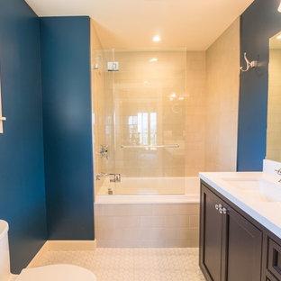 Modelo de cuarto de baño con ducha, tradicional, de tamaño medio, con armarios estilo shaker, puertas de armario de madera en tonos medios, bañera empotrada, combinación de ducha y bañera, sanitario de dos piezas, baldosas y/o azulejos blancos, baldosas y/o azulejos de cemento, paredes azules, suelo de linóleo, lavabo bajoencimera y encimera de cuarcita