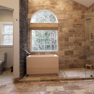 На фото: большая главная ванная комната в восточном стиле с плоскими фасадами, японской ванной, открытым душем, раздельным унитазом, коричневой плиткой, серыми стенами, полом из травертина, настольной раковиной и плиткой из травертина с