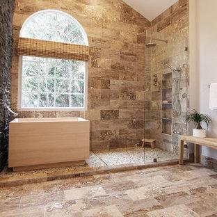 Esempio di una grande stanza da bagno padronale etnica con ante lisce, ante nere, vasca giapponese, doccia aperta, WC a due pezzi, piastrelle marroni, piastrelle in pietra, pareti grigie, pavimento in travertino e lavabo a bacinella
