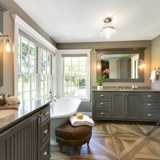 Foto de cuarto de baño principal, de estilo de casa de campo, grande, con armarios con puertas mallorquinas, puertas de armario grises, bañera exenta, paredes grises, suelo de madera en tonos medios, lavabo bajoencimera, encimera de granito, suelo marrón y encimeras marrones