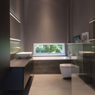 Photo of a medium sized contemporary ensuite bathroom in Oxfordshire with flat-panel cabinets, black cabinets, a built-in bath, a corner shower, grey tiles, porcelain tiles, grey walls, porcelain flooring, a vessel sink, grey floors, black worktops, a single sink and a built in vanity unit.