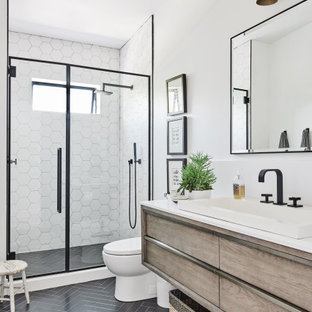 Example of a mid-sized beach style 3/4 white tile and ceramic tile ceramic tile and black floor alcove shower design in Los Angeles with a one-piece toilet, white walls, a drop-in sink, quartz countertops, a hinged shower door, white countertops, flat-panel cabinets and light wood cabinets