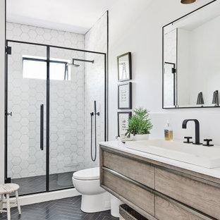 ロサンゼルスの中くらいのビーチスタイルのおしゃれなバスルーム (浴槽なし) (アルコーブ型シャワー、一体型トイレ、白いタイル、セラミックタイル、白い壁、セラミックタイルの床、オーバーカウンターシンク、クオーツストーンの洗面台、黒い床、開き戸のシャワー、白い洗面カウンター、フラットパネル扉のキャビネット、淡色木目調キャビネット) の写真
