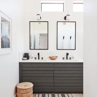 Ispirazione per una stanza da bagno padronale minimal di medie dimensioni con ante marroni, doccia alcova, WC monopezzo, pareti bianche, top in quarzo composito, porta doccia a battente, top bianco, parquet chiaro, lavabo integrato e pavimento marrone