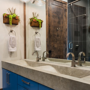 Example of a mountain style bathroom design in Salt Lake City with flat-panel cabinets, blue cabinets, white walls, an integrated sink, concrete countertops and gray countertops