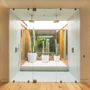 Modernes Badezimmer En Suite mit Doppeldusche, weißen Fliesen, weißer Wandfarbe, hellem Holzboden, Beton-Waschbecken/Waschtisch, braunem Boden und Falttür-Duschabtrennung in Los Angeles