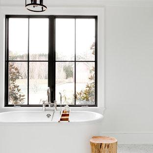 ニューヨークの広い北欧スタイルのおしゃれなマスターバスルーム (置き型浴槽、白い壁、グレーの床、家具調キャビネット、黒いキャビネット、アルコーブ型シャワー、グレーのタイル、白いタイル、石スラブタイル、大理石の床、アンダーカウンター洗面器、大理石の洗面台、開き戸のシャワー) の写真