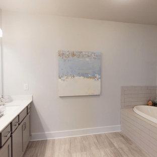 Imagen de cuarto de baño principal, contemporáneo, de tamaño medio, con armarios con paneles empotrados, puertas de armario beige, bañera encastrada, ducha empotrada, sanitario de una pieza, baldosas y/o azulejos beige, baldosas y/o azulejos de cerámica, paredes beige, suelo laminado, lavabo encastrado, encimera de acrílico, suelo beige, ducha con puerta con bisagras y encimeras blancas