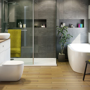 This is an example of a large contemporary ensuite bathroom in Hampshire with an integrated sink, open cabinets, white cabinets, laminate worktops, a one-piece toilet, grey tiles, black walls, porcelain flooring, a freestanding bath and a corner shower.