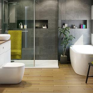 Cette image montre une grand salle de bain principale design avec un lavabo intégré, un placard sans porte, des portes de placard blanches, un plan de toilette en stratifié, un WC à poser, un carrelage gris, un mur noir, un sol en carrelage de porcelaine, une baignoire indépendante et une douche d'angle.