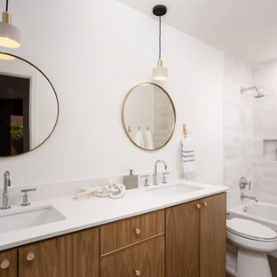 Design ideas for a medium sized scandinavian family bathroom in Phoenix with flat-panel cabinets, light wood cabinets, a shower/bath combination, a two-piece toilet, white tiles, ceramic tiles, white walls, concrete flooring, a submerged sink, engineered stone worktops, white worktops, a wall niche, double sinks and a floating vanity unit.
